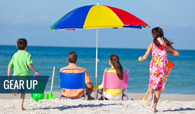 A family with beach rental gear - umbrellas, chairs, beach toys